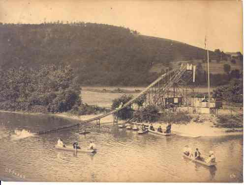 """Shoot the chute."" The new driving guide tour includes a visit to the site of a former wooden water toboggan used in the early 1900s near today's Fitch's Bridge in Big Flats where locals went to ""shoot the chute"" and ride a wooden sled down the toboggan into the river. (Photo provided by Friends of the Chemung River Watershed). Notice the boat paddlers in suits and ties."